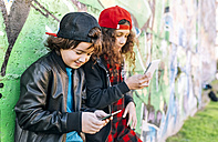 Two children leaning against graffiti wall using smartphones - MGOF02790