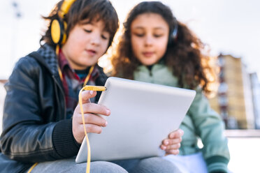Two children listening music with headphones and tablet - MGOF02793