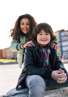 Portrait of smiling boy with his girlfriend in the background - MGOF02799