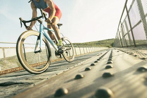 Athlete riding bicycle on a bridge - JASF01465