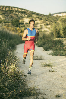 Athlete running in rural landscape - JASF01468