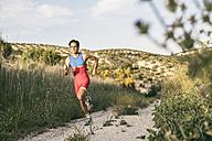 Athlete running in rural landscape - JASF01471