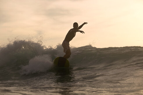 Indonesia, Bali, surfer at sunset - KNTF00605