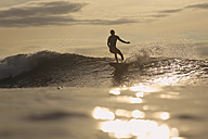 Indonesia, Bali, surfer at sunset - KNTF00611