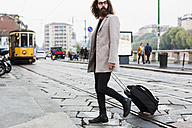 Stylish young man with suitcase crossing tramway - MAUF00929