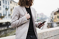 Stylish young man outdoors holding cell phone - MAUF00932
