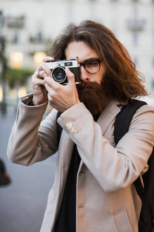 Stylish young man outdoors taking pictures with old-fashioned camera - MAUF00944