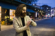 Stylish young man outdoors at night checking the time - MAUF00965