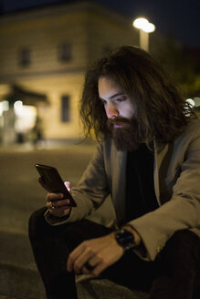 Stylish young man outdoors in the city at night looking at cell phone - MAUF00971