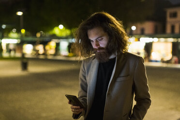 Stylish young man outdoors in the city at night looking at cell phone - MAUF00974