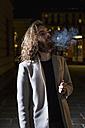 Stylish young man smoking outdoors at night - MAUF00977