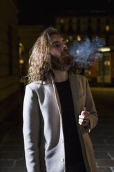 Stylish young man smoking outdoors at night - MAUF00977