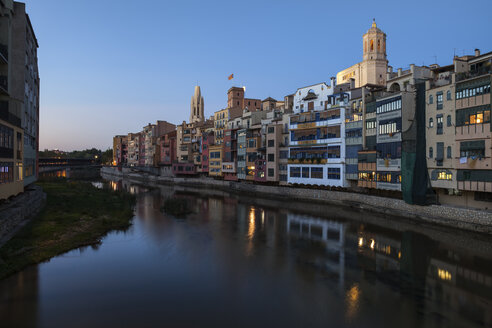 Spain, Girona, Basilica of San Felix and Cathedral of Santa Maria behind houses at Onyar River in the evening - ABOF00148