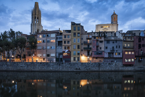 Spain, Girona, Basilica of San Felix and Cathedral of Santa Maria behind houses at Onyar River in the evening - ABOF00151