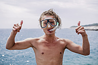Portrait of smiling young man with diving goggles and snorkel showing Rock And Roll Sign - WVF00778