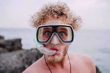 Portrait of young man with diving goggles and snorkel pulling funny faces - WVF00781