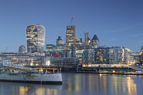 UK, London, skyline with office towers and HMS Belfast museum ship at dusk - GF00938