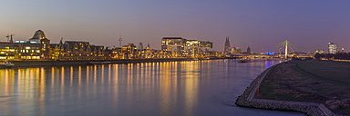 Germany, Cologne, panoramic view of the lighted city with Rhine River in the foreground - WGF01040