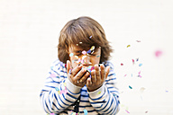 Boy blowing colorful confetti from there hands - VABF01010