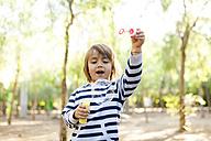 Boy makining soap bubbles in park - VABF01013