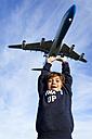 Boy reaching for landing airplane - VABF01019