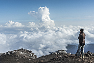 Italy, Sicily, hiker standing on Mount Etna looking at view - HWOF00204