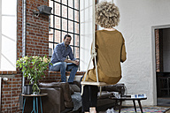 Young woman sitting on swing in living room, talking to man - RBF05539