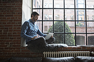 Mature man sitting on window sill, using laptop - RBF05542