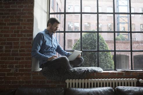 Mature man sitting on window sill, using laptop - RBF05542