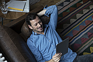 Man lying on couch, using digital tablet - RBF05554