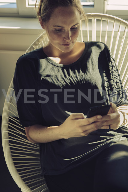 Young woman sitting in a chair looking at her cell phone - MFF03467 - Mareen Fischinger/Westend61