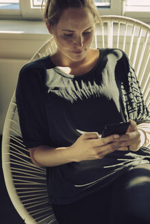 Young woman sitting in a chair looking at her cell phone - MFF03467