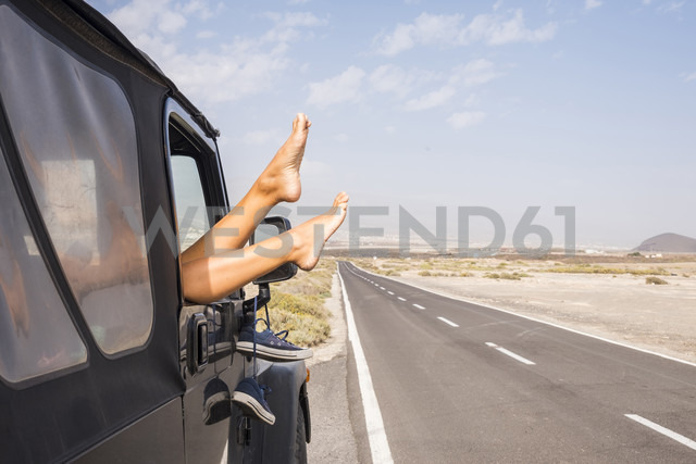 Spain, Tenerife, legs of woman leaning out of car window - SIPF01324