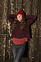 Portrait of relaxed young woman wearing winter fashion leaning against wooden wall - SARF03118