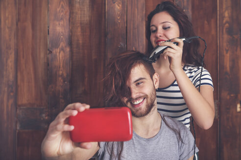 Young man taking a selfie while getting a haircut by his girlfriend with hair cutting machine - RTBF00586