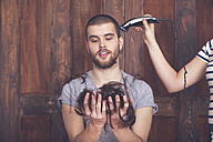 Portrait of young man getting a haircut by his girlfriend with hair cutting machine - RTBF00589