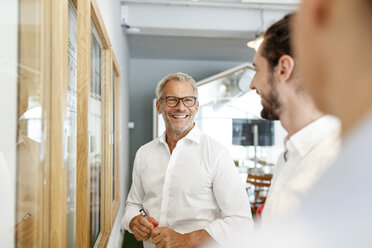 Smiling businessman looking at colleagues in office - PESF00410
