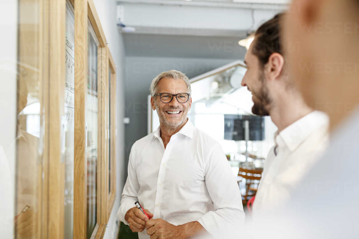 Smiling businessman looking at colleagues in office - PESF00410 - Peter Scholl/Westend61