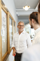 Smiling businessman looking at colleagues in office - PESF00413