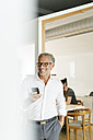 Smiling businessman with cell phone in office - PESF00416