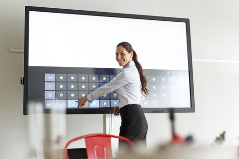 Businesswoman using projection of a keyboard with emoticons in conferene room - PESF00422