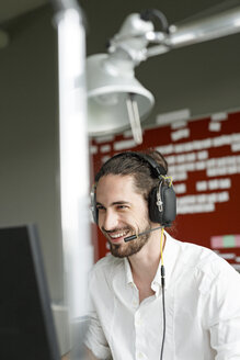 Smiling man in office with headset - PESF00434