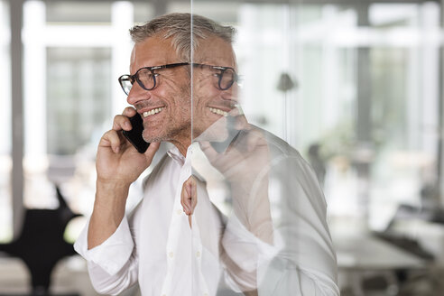 Smiling businessman on cell phone in office - PESF00440