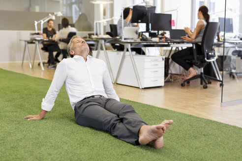 Businessman sitting on carpet in office - PESF00458