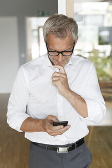 Businessman checking cell phone in office - PESF00476