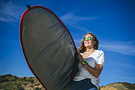 Happy young woman with surfboard on the beach - KIJF01081