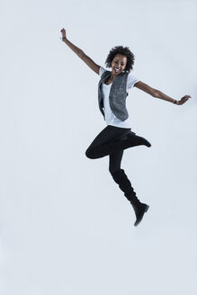 Woman jumping in the air in front of grey background - UUF09768
