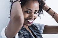 Portrait of smiling young woman with hands in her hair - UUF09771