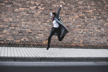Young woman with headphones and backpack jumping in the air in front of brick wall - UUF09789