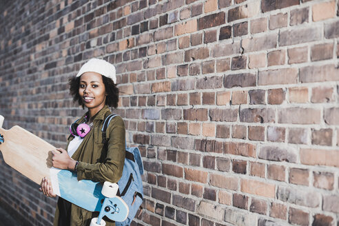 Portrait of smiling young woman with headphones, skateboard and backpack in front of brick wall - UUF09795
